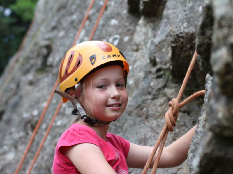 portrait d'une fillette faisant de l'escalade en colonie de vacances à la montagne