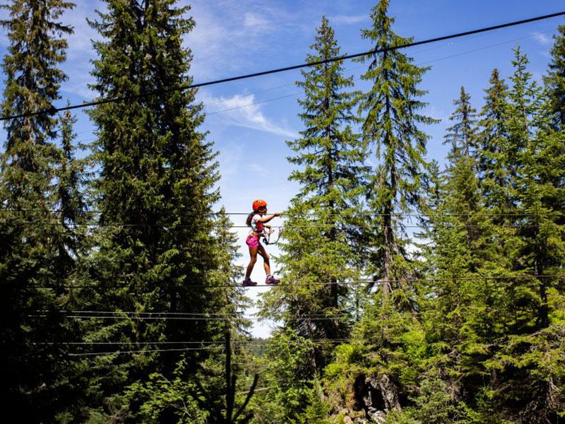 adolescente sur un parcours d'accrobranche à la montagne pendant une colonie de vacances