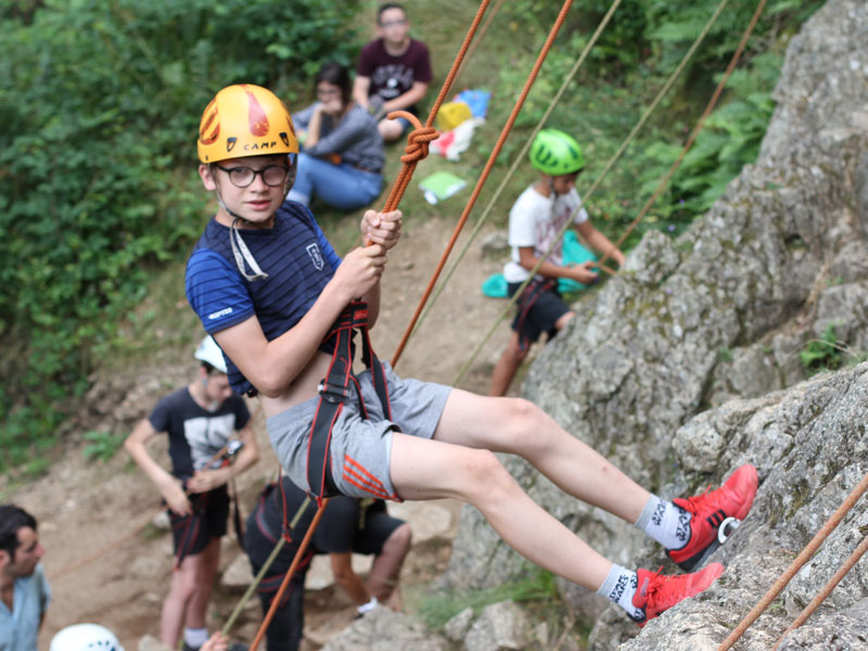 jeune garçon en descente en rappel en colonie de vacances à la montagne