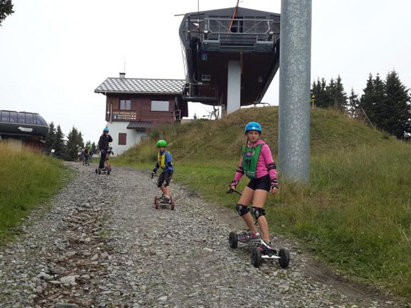 groupe de préadolescents faisant de la luge d'été à la montagne lors d'une colonie de vacances