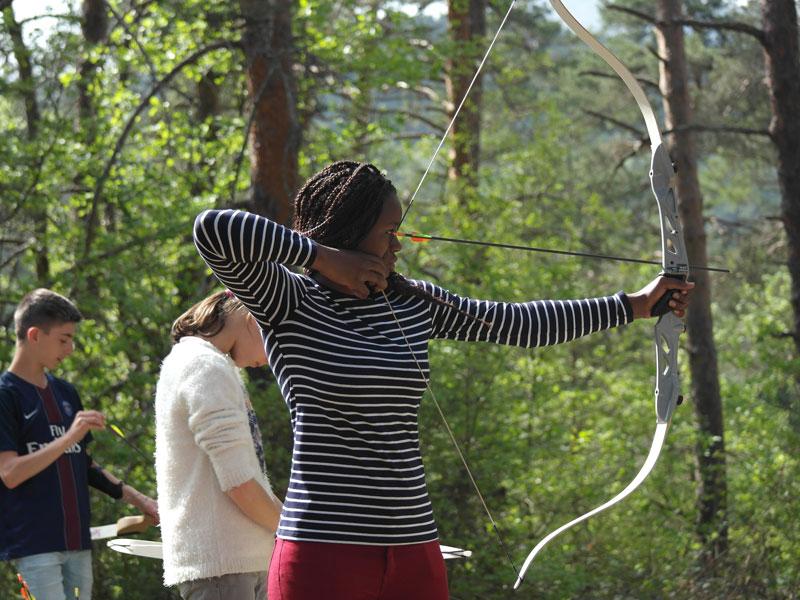jeune adolescente se perfectionnant au tir à l'arc en colonie de vacances à la montagne