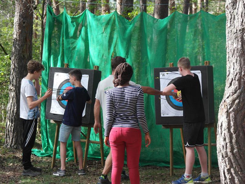 Enfants et adolescents découvrant le tir à l'arc cet automne en colonie de vacances