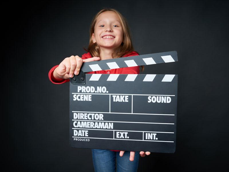 fillette tenant un clap de cinéma durant une colonie de vacances cinema