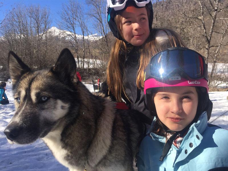 portrait de fillettes avec leur chien de traineau en colonie de vacances cet hiver