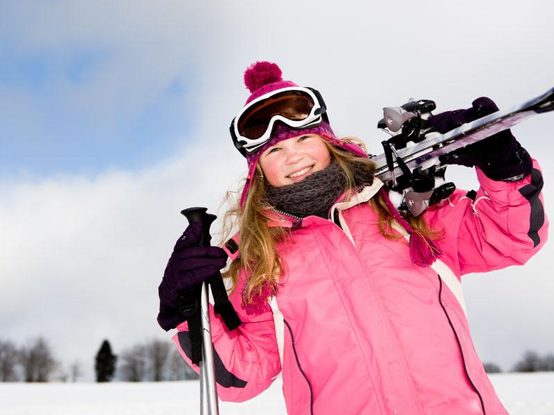 jeune fille avec son équipement de ski sur les pistes de colonie de vacances