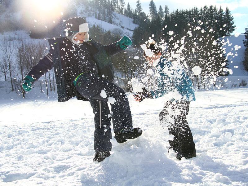 enfants jouant avec la neige en colonie de vacances