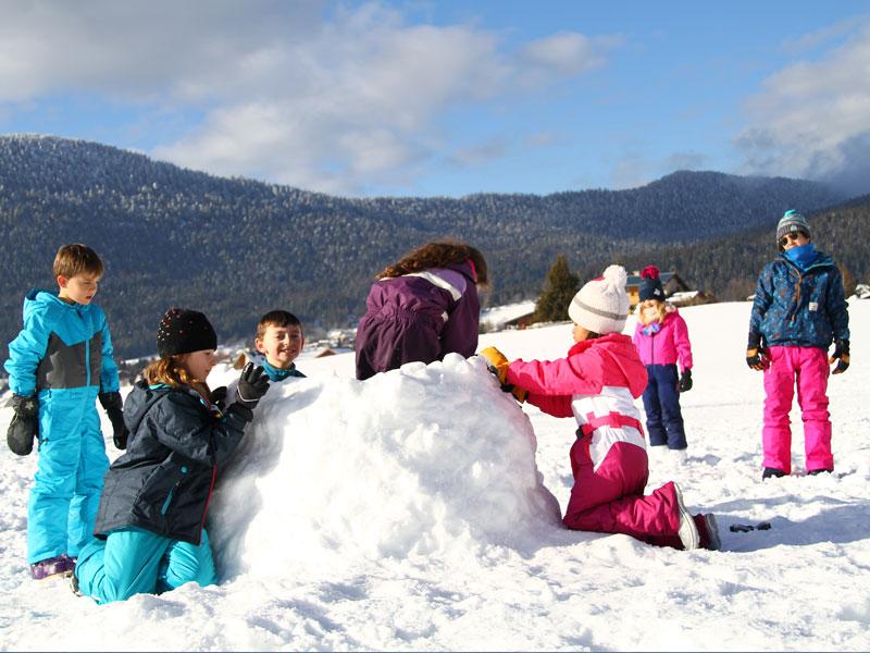 enfants construisant un igloo en colo cet hiver