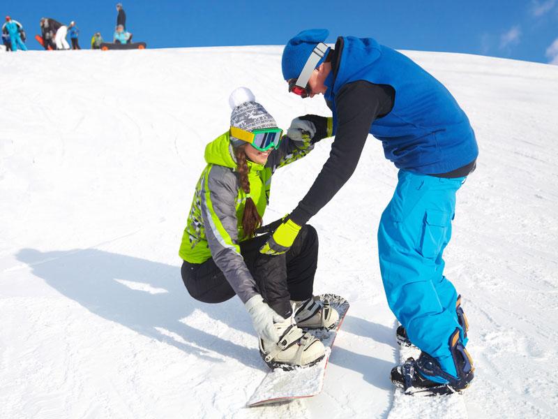 ado apprenant à faire du snowboard cet hiver en colonie de vacances