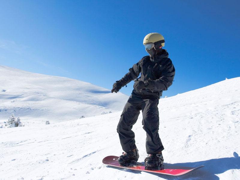 ado à snowboard en colo sur les pistes de ski