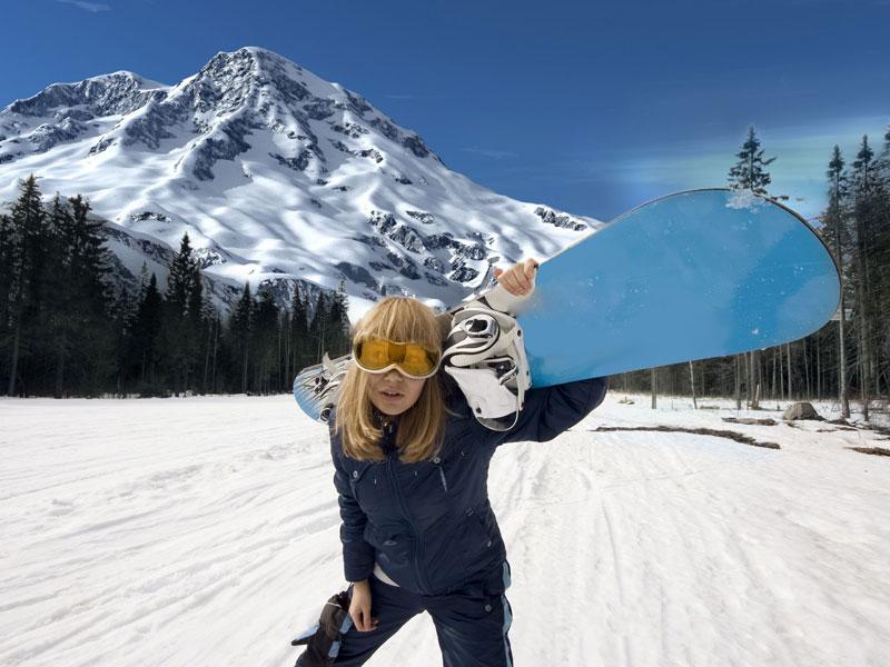 adolescente portant sa planche de snowboard en colo cet hiver