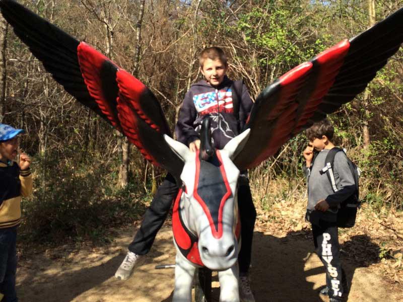 Enfant sur une statue de cheval ailé à Défi'planet en colonie de vacances cet automne