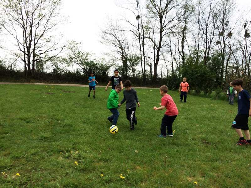 Groupe d'enfants jouant au football cet automne en colonie de vacances