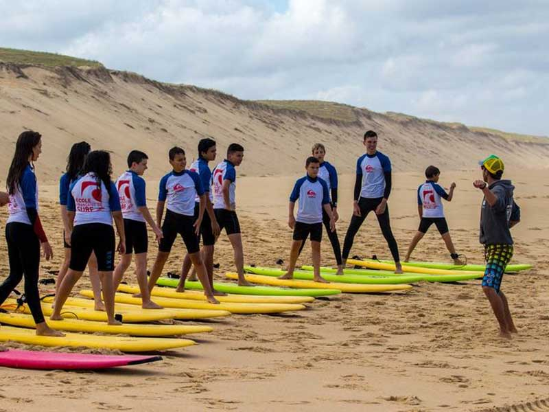Groupe d'adolescents sur les planches de surf en colo cet automne