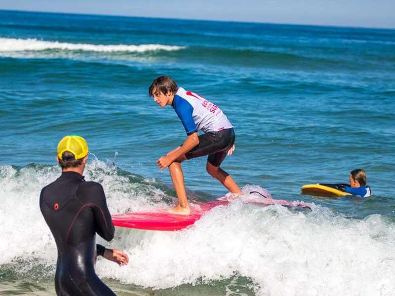 Adolescent apprenant à faire du surf en colonie de vacances cet automne