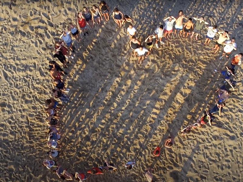 Groupe d'enfants formant un coeur sur la plage en colo en corse