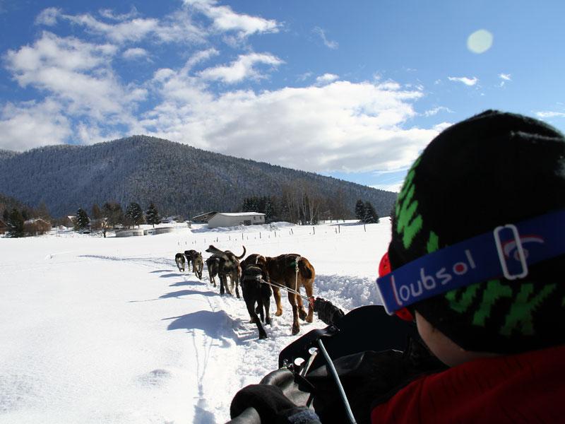 Enfant sur un traineau en balade à la montagne en colonie de vacances