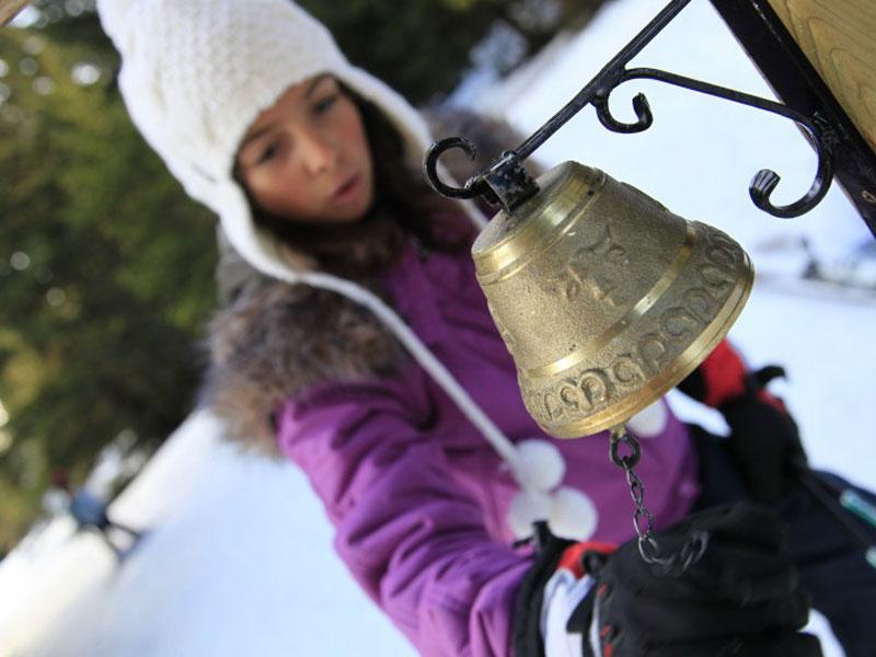 Jeune fille jouant avec la cloche d'un chalet en colonie de vacances à la neige