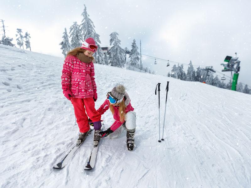 fillettes apprenant à chausser leurs skis en colonie de vacances à la neige
