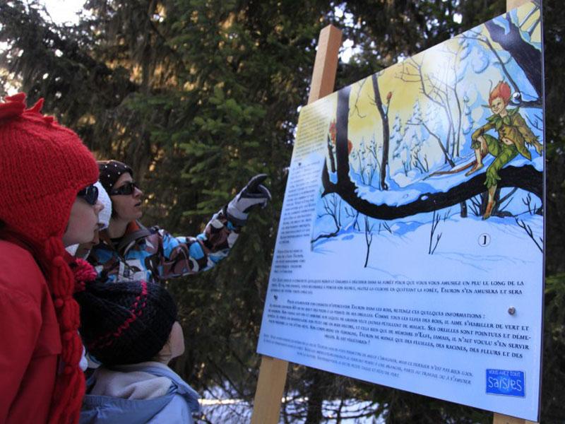animatrice de colo montrant le chemin des pistes de ski à une enfant en colonie de vacances