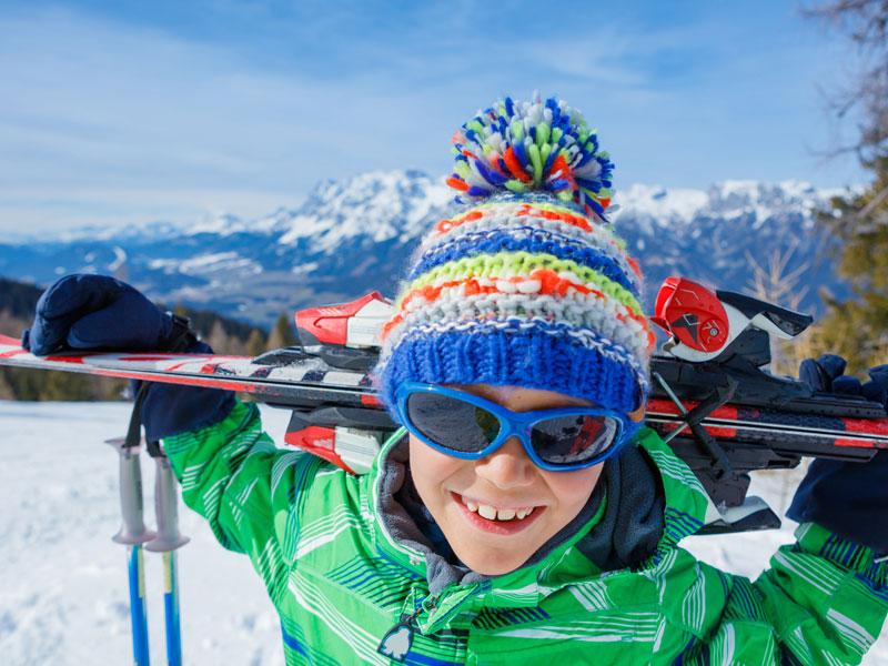 Portrait d'un jeune garçon sur les pistes de ski portant ses ski sur ses épaules en colo