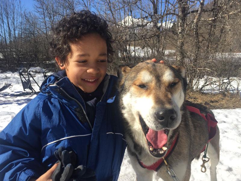 portrait d'un enfant avec son chien de traineau en colonie de vacances d'hiver