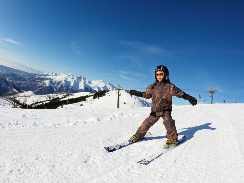 enfant de 8 ans apprenant à skier en colonie de vacances cet hiver