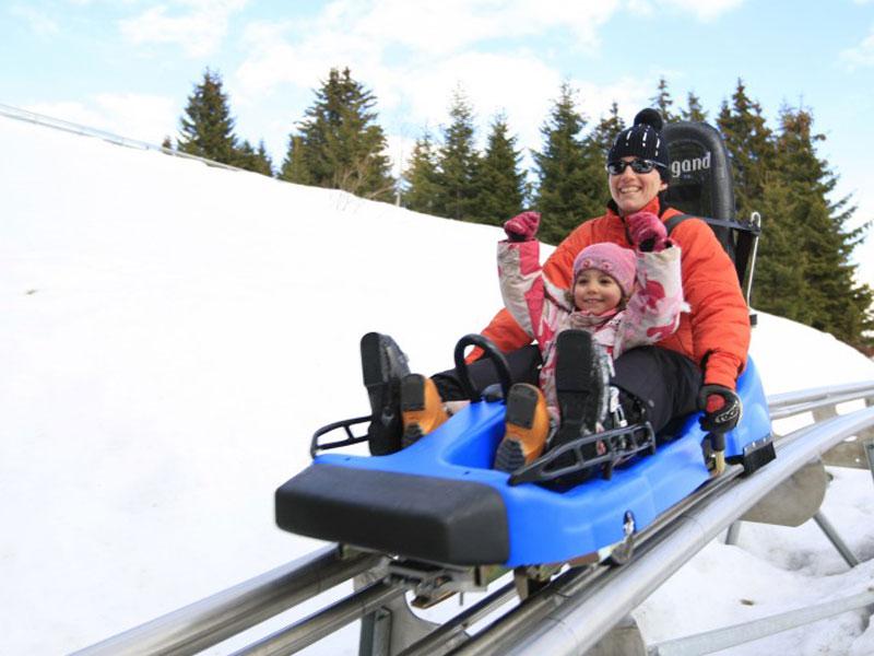 Enfant et son animatrice de colonie de vacances faisant de la luge mountain twister