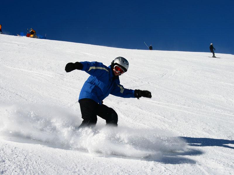 enfant faisant du snowboard en colonie de vacances d'hiver