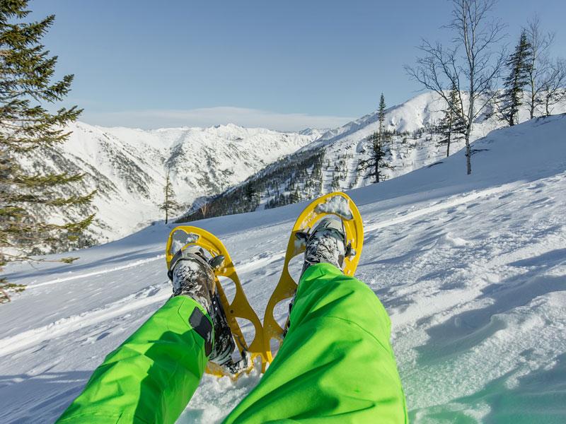 enfant allongé sur la neige lors d'une randonnée en raquettes en colonie de vacances cet hiver