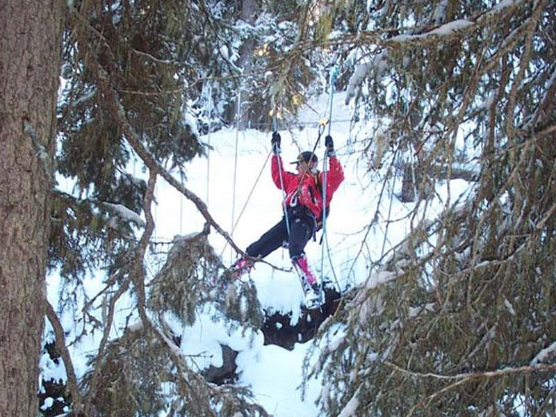 jeune ado faisant de l'accrobranche à la neige cet hiver en colonie de vacances