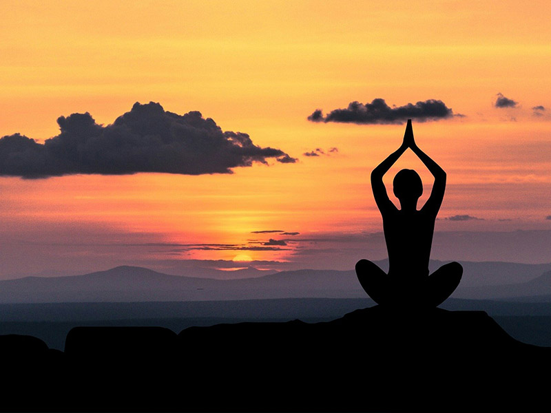 Jeune femme faisant du yoga devant un coucher de soleil en colo