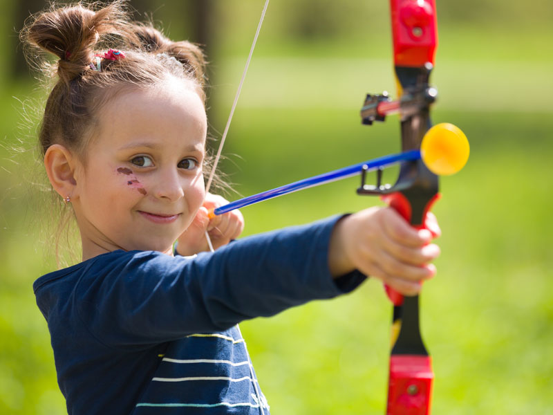 portrait d'une fillette jouant au tir à l'arc flu flu en colo