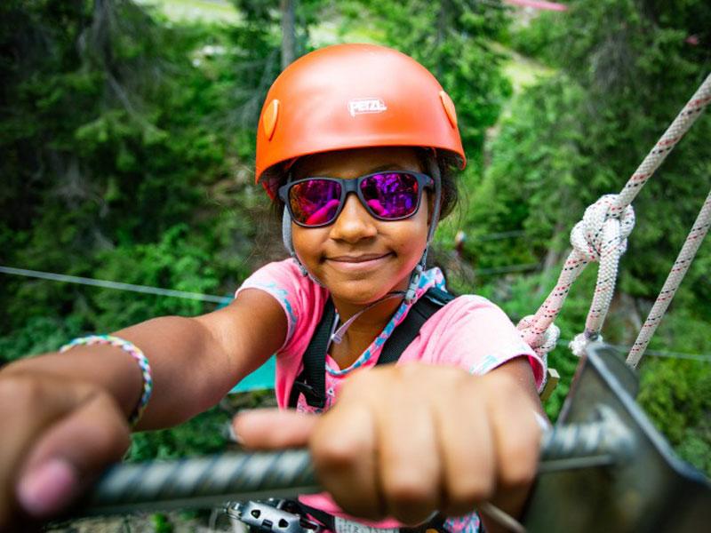 Portrait d'une fillette portant un casque et faisant de l'accrobranche en colonie