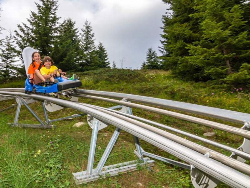 Enfants et ados faisant de la luge sur rails en colo à paques