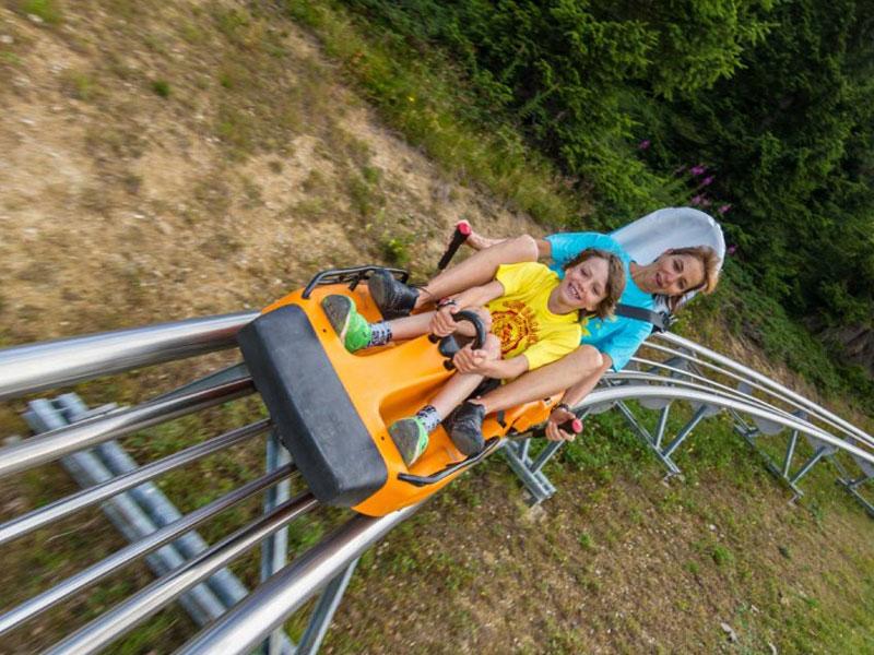 enfants en colo faisant de la luge sur rails