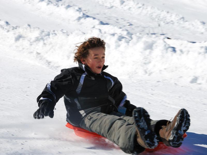 Enfant faisant de la luge à la neige en colo ce printemps