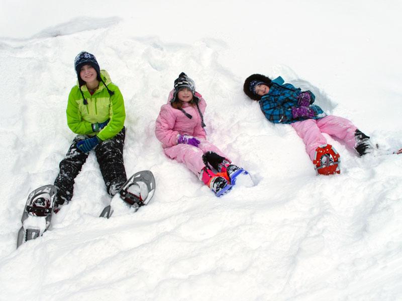 trois enfants jouant dans la neige en colonie de vacances de printemps