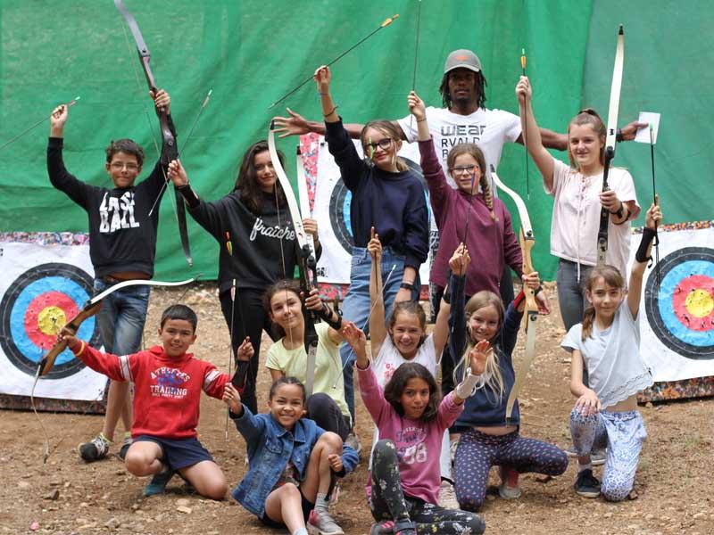 Groupe d'enfants en colo pratiquant le tir à l'arc
