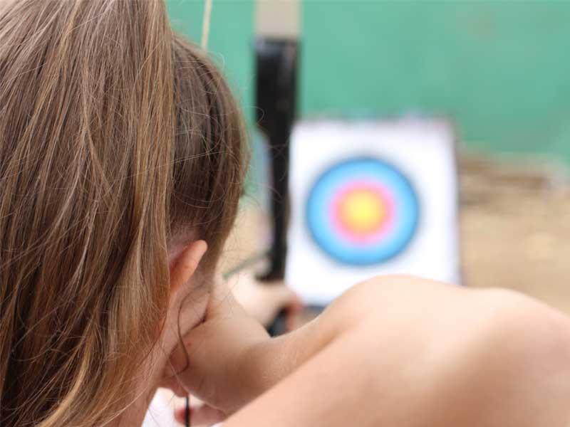 Jeune fille visant une cible en tir à l'arc