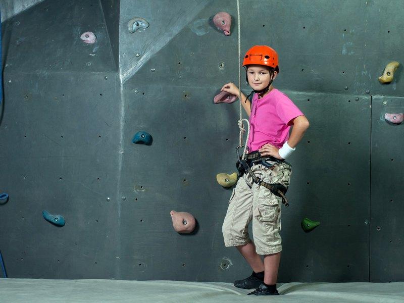 Ado au pied d'un mur d'escalade