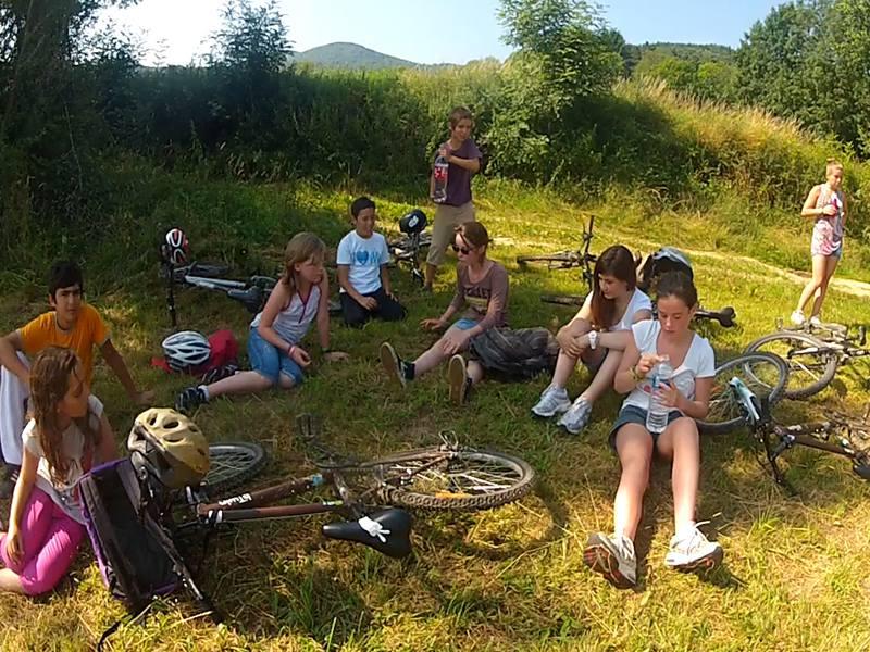 Groupe d'enfants en repos dans l'herbe après une randonnée à vélo