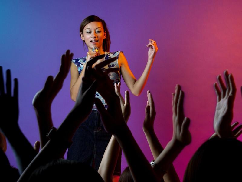Enfant en train de chanter sur scène face au public