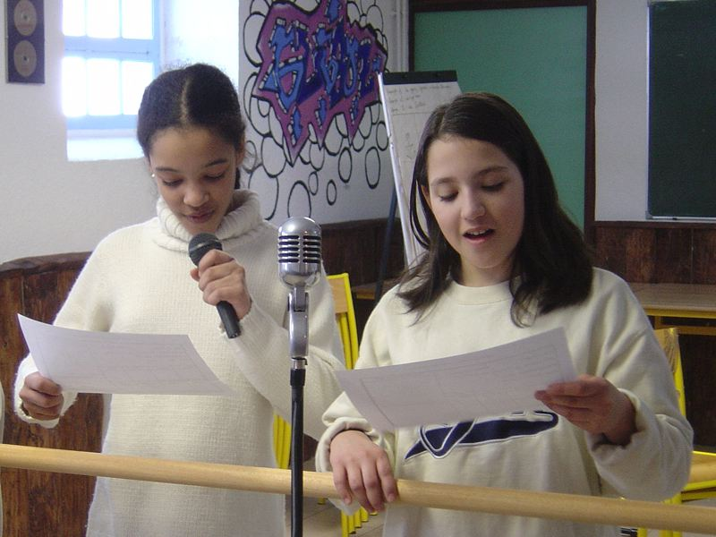 Enfants en train de chanter s'aidant de paroles