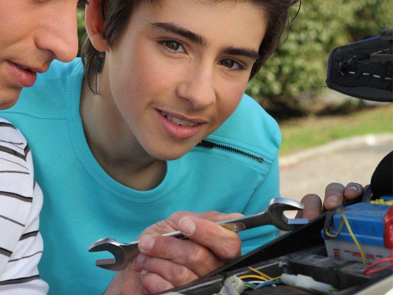 Préado apprenant la mécanique sur une moto