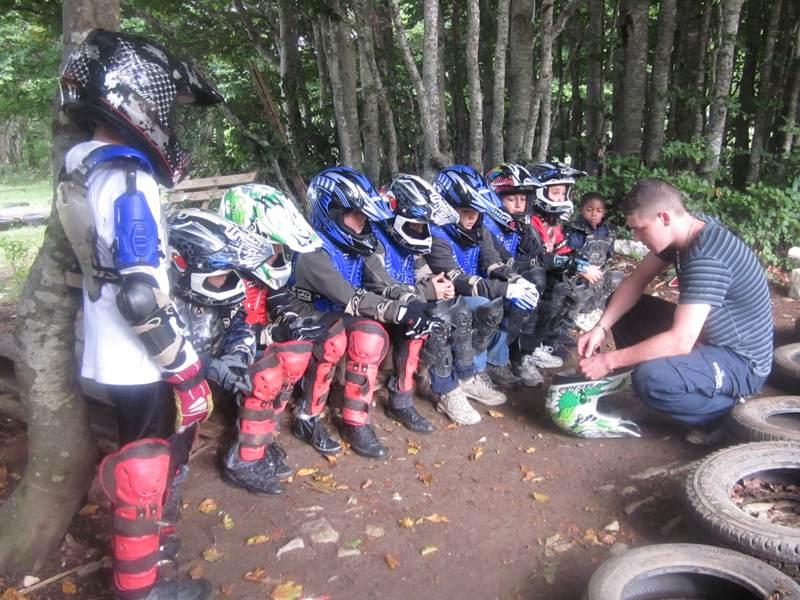Groupe d'enfants avec équipement de moto suivant une formation sur la motocross en colonie de vacances
