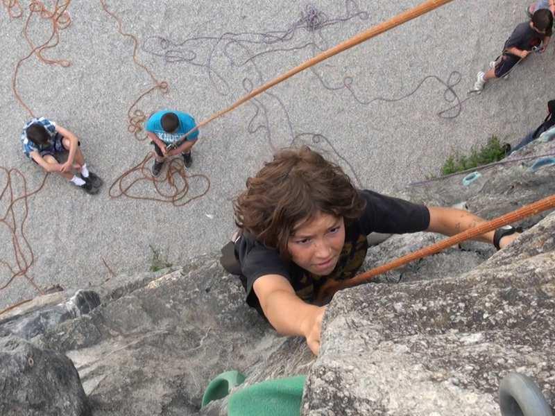 Enfant pratiquant l'escalade sur roche