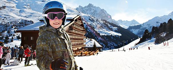 Enfant heureux en colonie de vacances au ski à Courchevel cet hiver