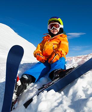 Jeune enfant débutant au ski en colonie de vacances ski assis dans la neige