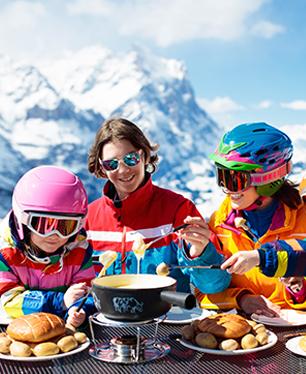 Groupe d'enfants et ados mangeant une fondue savoyarde cet hiver en colonie de vacances ski