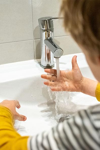 Enfant se lavant les mains en colonie de vacances